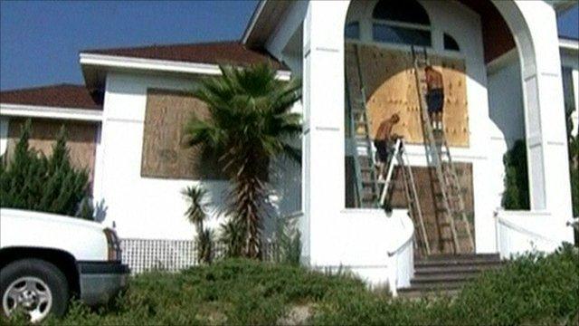 Workmen boarding up windows of a house
