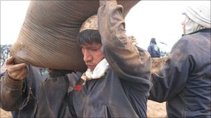 Workers carry more than 100 50kg sacks a day