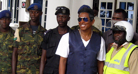 Jermaine Jackson (second right) poses for photos with Gambia soldiers and police officers