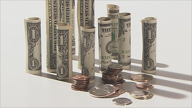 Rolled up US banknotes and coins