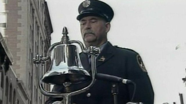 A policeman tolls a bell to mark the moment when the first plane struck