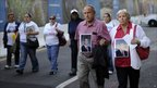 Relatives of 9/11 victims carry their photographs in New York (11 Sept 2010)