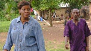 Zainab Bangura walks through a village in Sierra Leone