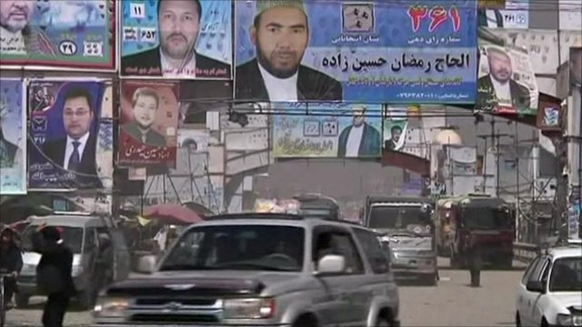 Cars driving under campaign posters