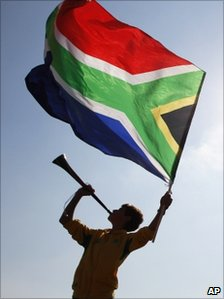 Supporter waves South African flag as he blows a vuvuzela