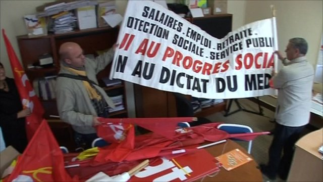 Room with campaign materials and men holding up banner