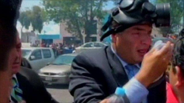 Ecuador's President Rafael Correa in a gas mask