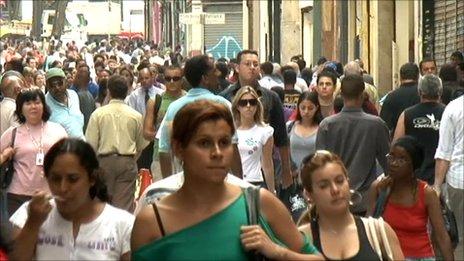 Brazilians walk along a main street in Sao Paulo, September 2010