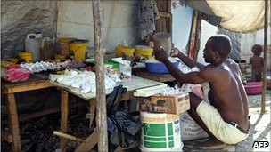 A man prepares food at a camp in Port-au-Prince, Haiti (10 Sept 2010)