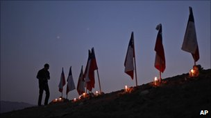 A man stands next to to Chilean flags representing 33 trapped miners outside the San Jose mine in Copiapo, Chile