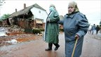 Two women walking past a house damaged by the red toxic sludge in the village of Kolontar, Hungary.