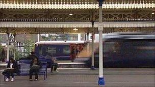 Passengers on a train platform as a train drives past