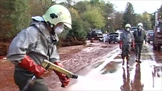 Clean up worker spraying sludge