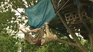 A protester climbing a rope to a tree house
