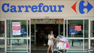 A Thai shopper leaving a French retail giant Carrefour supermarket in Bangkok