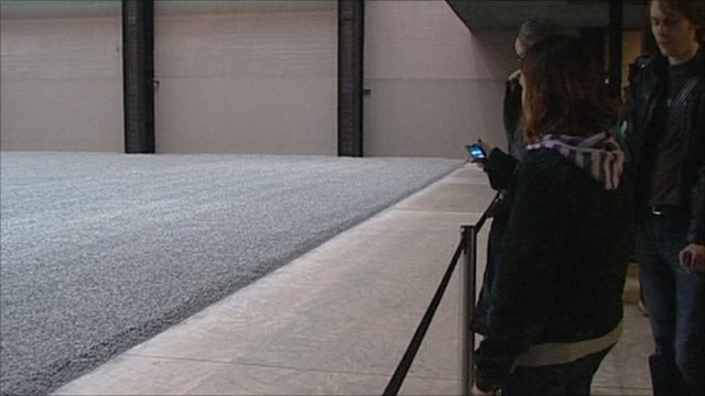 Visitors look at porcelain seeds at Tate gallery