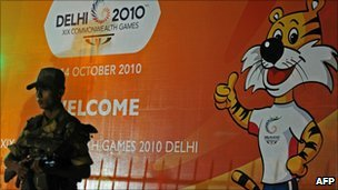 Indian policeman stands guard beside a banner for the 2010 Commonwealth Games outside a hotel in New Delhi on 1 October 2010