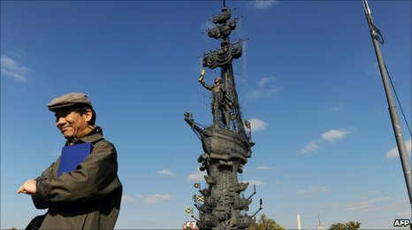A man stands in front of the Peter the Great statue in Moscow