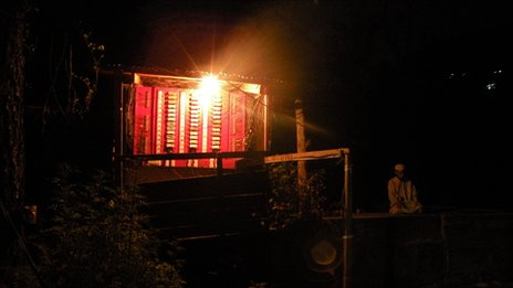 A man prays in darkness as light shines on him from inside a hydropower generator