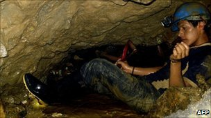 A miner tries to dig way through to reach two men trapped underground in Ecuador