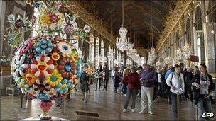 Visitors look at a Murakami work at Versailles