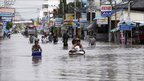 Residents carrying their belongings wade through floodwater in Nakhon Ratchasima province, northeast of Bangkok
