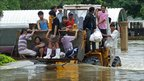 Flood-affected people ride a tractor through flood water in Thailand's Nakhon Ratchasima province