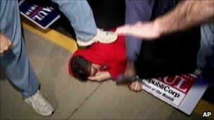 A Rand Paul supporter stepping on an activist at a Kentucky debate