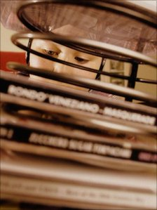 Boy listening to music behind stack of CDs