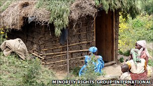 Batwa women outside a house