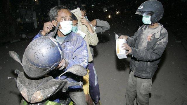 Villagers wear masks as ash falls