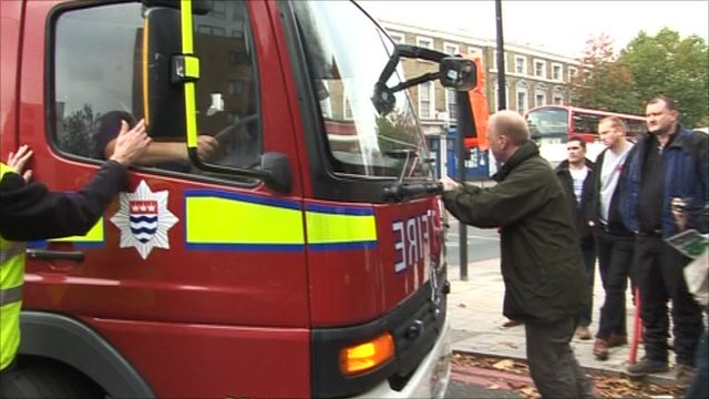 A man stands in front of a fire engine