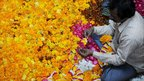 A man in Amritsar, India, strings marigold flowers together to make garlands for the upcoming Hindu festival of lights, Diwali.