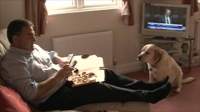 A man eating pizza in front of the television