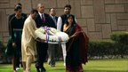 US President Barack Obama (L) and First Lady Michelle Obama participate in wreath laying ceremony at Raj Ghat, the memorial to Mahatma Gandhi, in New Delhi on November 8, 2010.