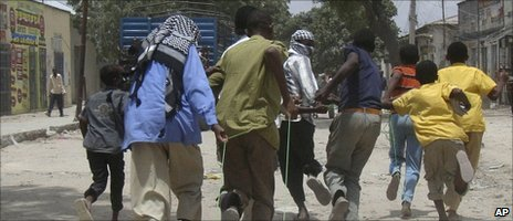 Somali residents drag a body through the streets of Mogadishu on 6 October 2010