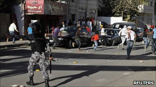 Jordanian riot police try to disperse members of two clans after they brawled in front of a polling station in Amman 9 November