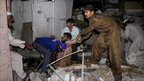 A Pakistan rescue worker and volunteers remove an injured man at the site of the bomb explosion in Karachi, Pakistan