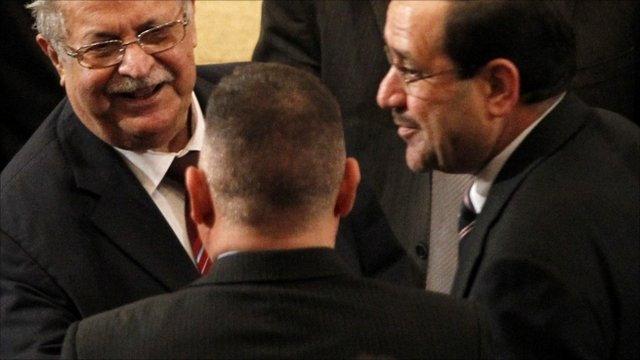 Iraq's President Jalal Talabani (left) and Prime Minister Nuri al-Maliki (right) talk during a parliament session in Baghdad