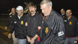 Viktor Bout (centre) arrives in New York, escorted by US federal agent (16 November 2010)