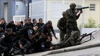 Army soldiers and policemen take position during an operation at Alemao slum in Rio de Janeiro November 28, 2010