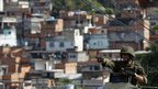 A soldier gestures from an armoured car as he moves inside the Complexo do Alemao slum