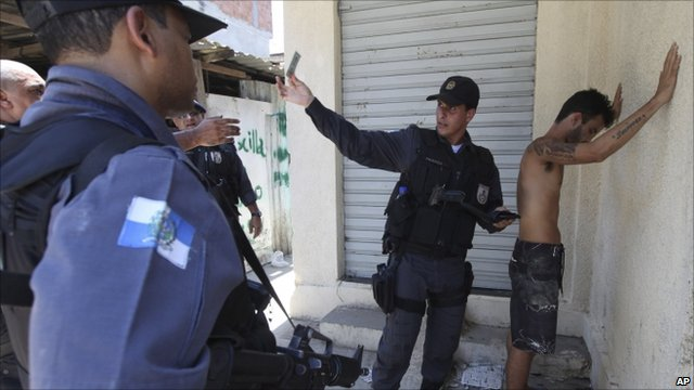 Police officer holds up suspect's ID during raid in Alemao favela