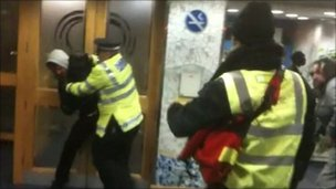 A police officer tackles a protester inside Lewisham town hall
