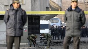Policemen stand guard as security personnel work on site of a blast in Bishkek