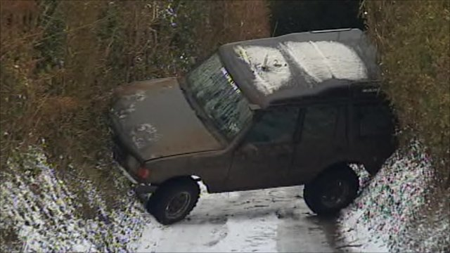Car wedged between embankments on a country lane