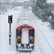 A train makes its way through the snow in Horley, Surrey as icy conditions cause further travel disruptions