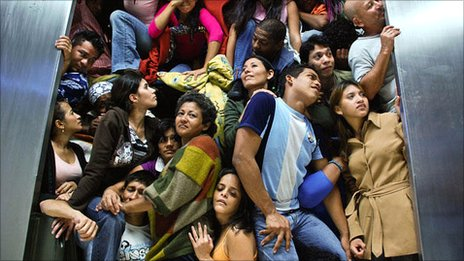 Prometeo Deportado still of people trying to squeeze out of the waiting room at the airport