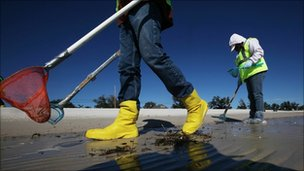 Workers clean tarballs from the BP oil spill on Waveland beach, Mississippi on 6 December 2010