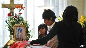 Relatives of murdered footballer Carlos Mercedes Vasquez mourn beside his coffin on 29 November 2010